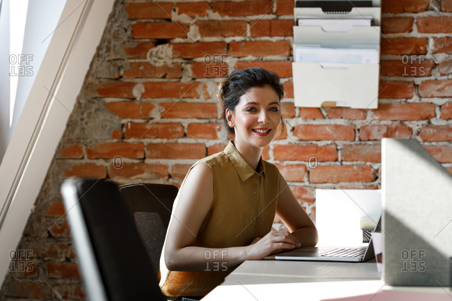 Portrait of beautiful young businesswoman standing at modern industrial office space and looking at camera.