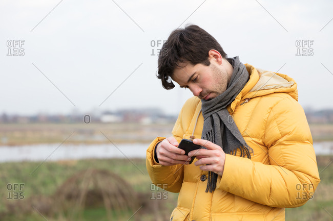 Male with scarf reading on mobile phone outdoors