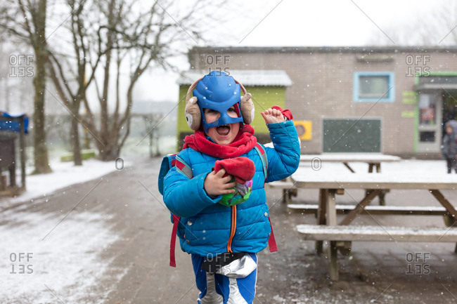 Young boy dressed as superhero playing in snow