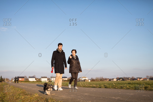 Grandmother and grandson walking dog in nature