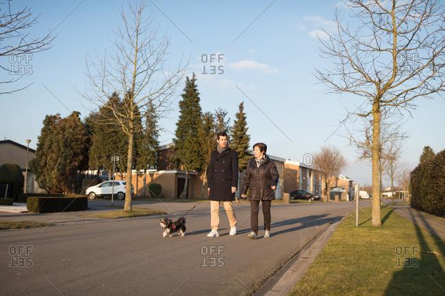 Grandmother and grandson walking dog in neighborhood