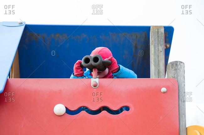 Boy looking through binoculars at playground