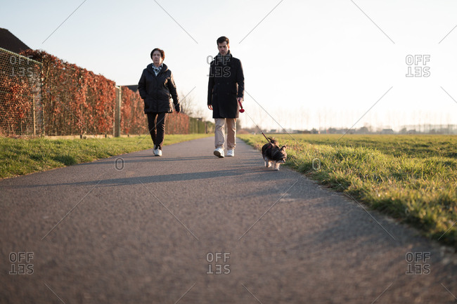 Senior woman and young man walking the dog in rural setting