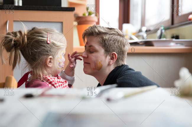 Girl painting on face of mother with fingers