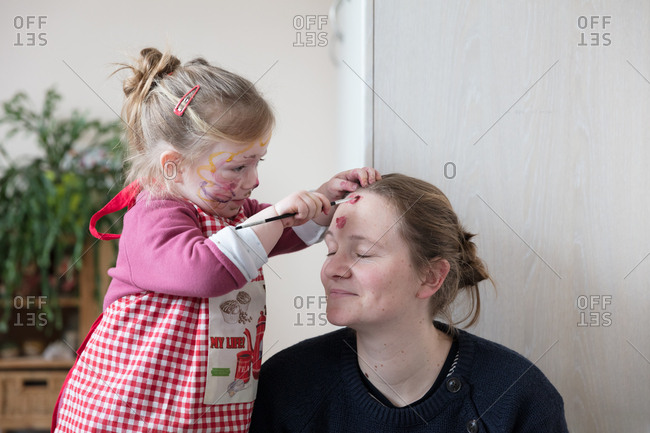 Daughter painting on face of mother