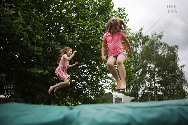 Two girls jumping high on trampoline together
