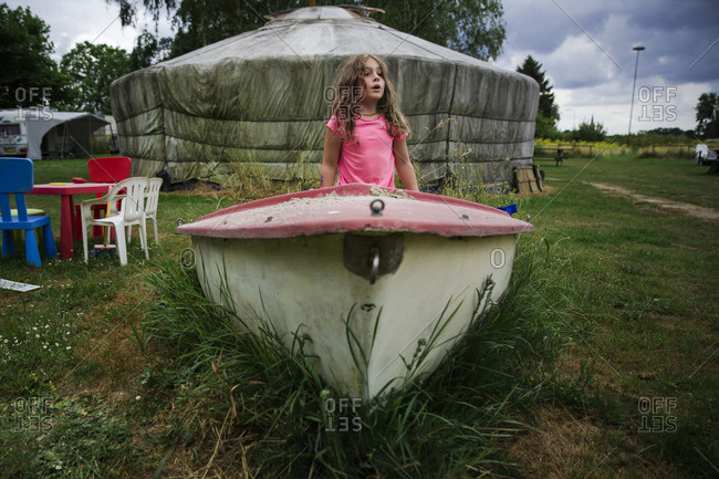 Girl playing in an old boat that has been converted into a sandbox at a campground with yurt