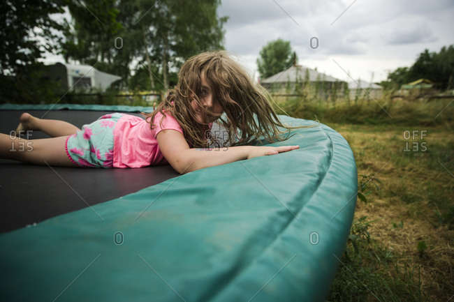 Girl with messy hair lying down on trampoline