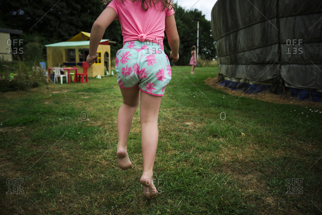 Rear view of barefoot girl running through campground