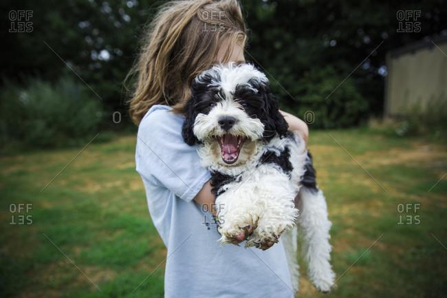 Boy holding yawning dog