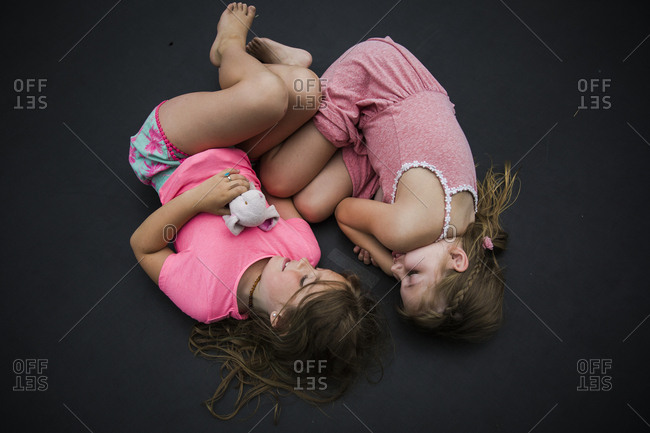 Two girls lying down on trampoline cuddling together