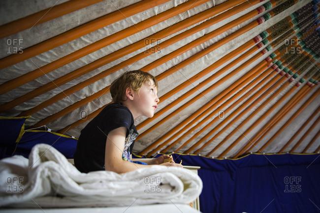 Boy sitting on top bunk inside yurt