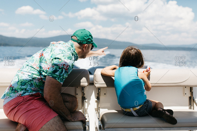 Father and daughter looking over the back of a boat on Lake Tahoe