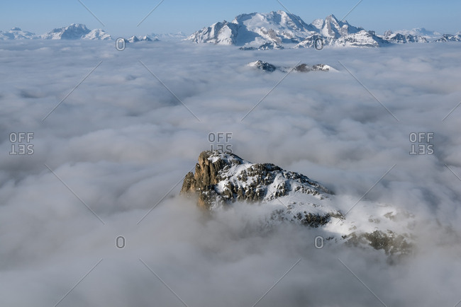 Cold and windy winter morning with the phenomenon of thermal inversion from the top of the mountain Lagazuoi towards the Marmolada glacier and Sella mount, Dolomites, Italy
