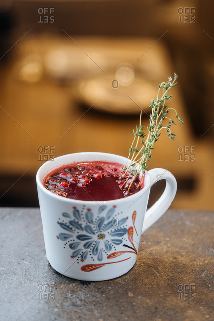 Mug with warm mulled drink with berries and herbs