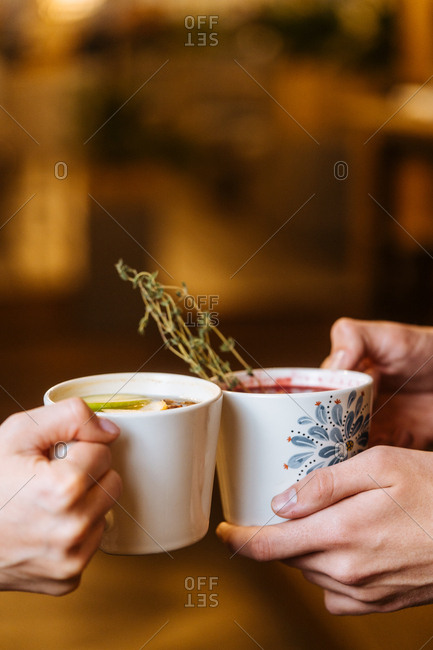Two people holding mugs with mulled warm drinks