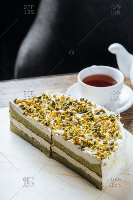 Cake topped with pistachios served with tea