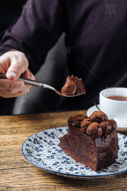 Person holding a fork with a bite of chocolate cake