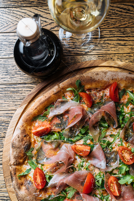 Gourmet pizza served with balsamic vinegar and white wine