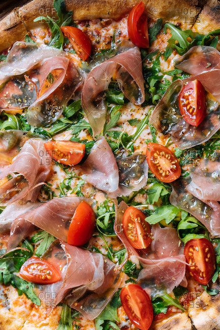 Close-up of pizza topped with prosciutto, tomatoes, and arugula