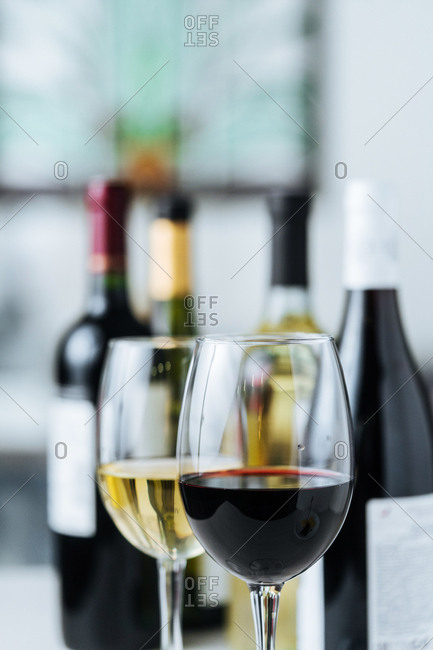 Two glasses with red and white wine and wine bottles