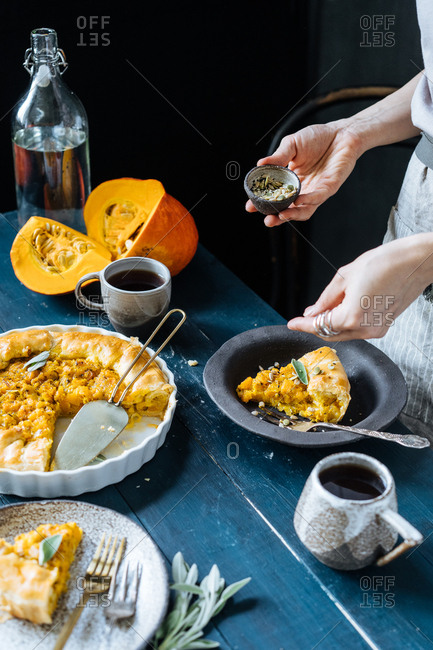 Person sprinkling seeds on top of piece of freshly baked squash cobbler