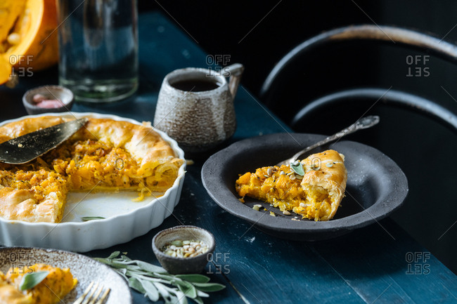 Slice of freshly baked squash cobbler garnished with sage and served with coffee