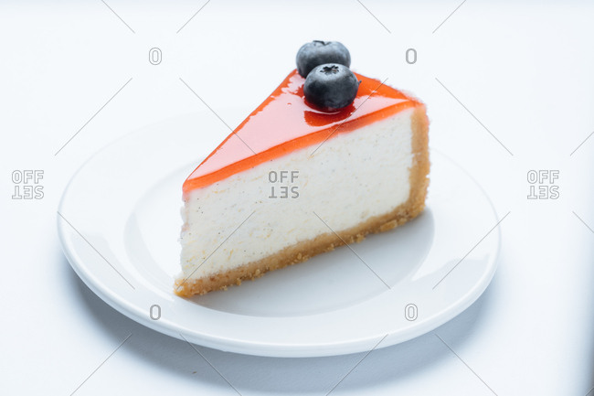 Single slice of cheesecake topped with blueberries