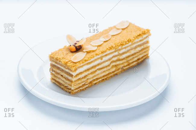 Piece of layered dessert topped with almonds