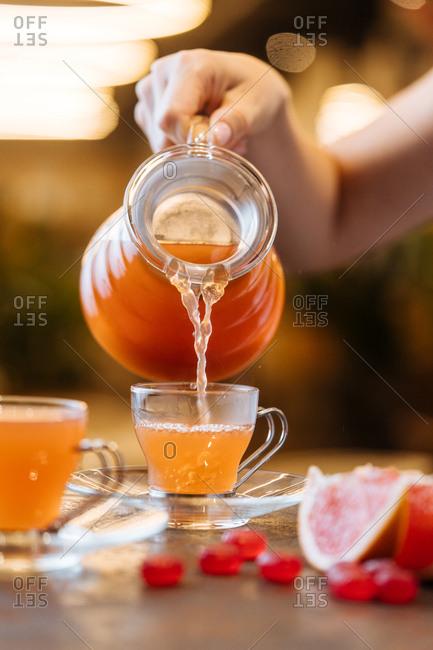 Woman pouring warm orange juice