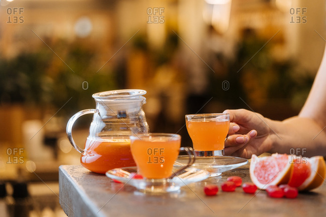 Woman holding glass of citrus juice