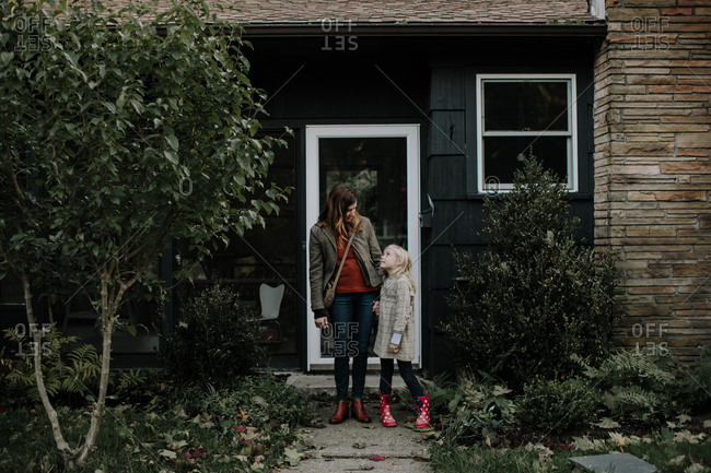 Mother and daughter standing by front door of house