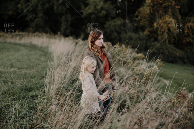 Mother and daughter standing in field looking away