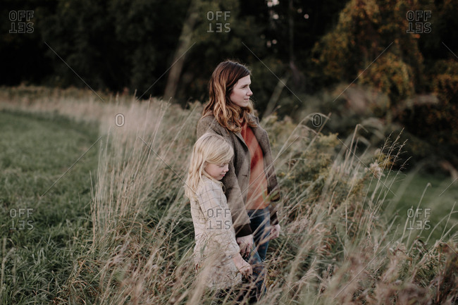 Mother and daughter standing together in field looking away