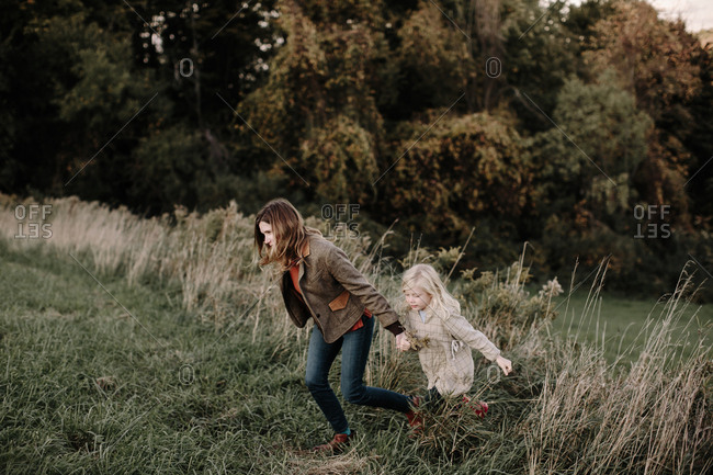 Mother and daughter running together in field looking away