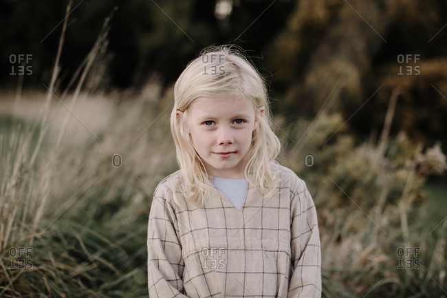 Portrait of young blonde girl alone in a field