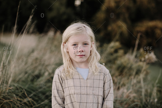 Portrait of blonde girl alone in a field