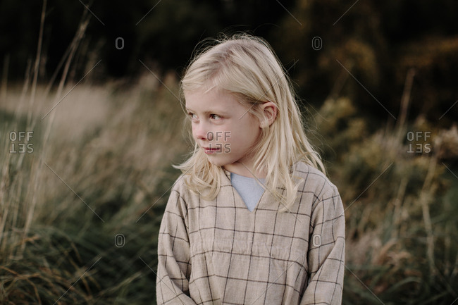 Young blonde girl alone in a field looking away