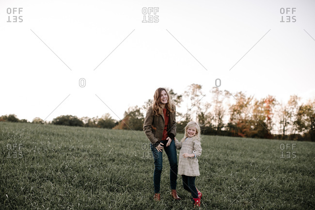 Mother and daughter together in field laughing