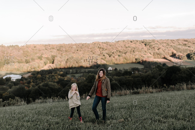 Mother and daughter laughing in the countryside