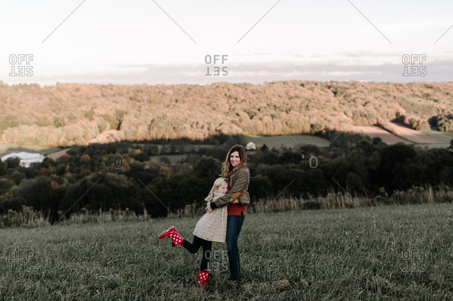 Girl hugging her mom in a field