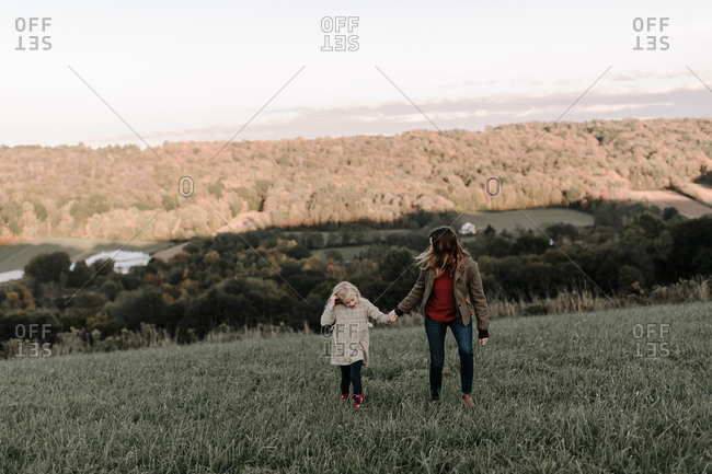Mother and daughter walking together in field looking away
