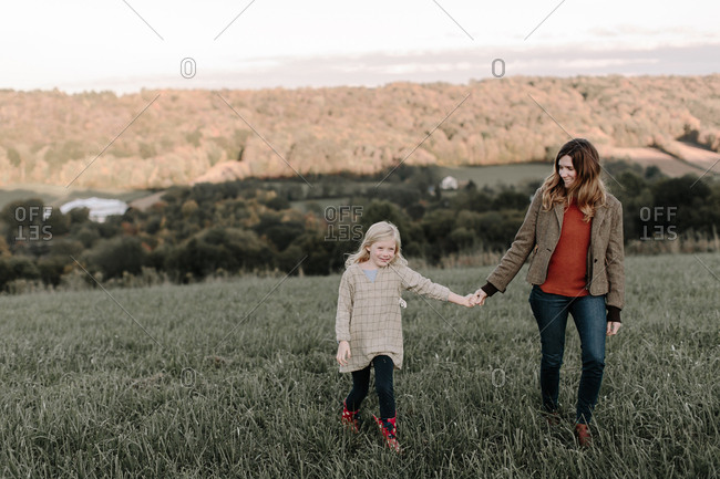 Mom and daughter walking together in field looking away