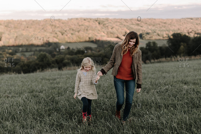 Mom and daughter walking hand in hand in field