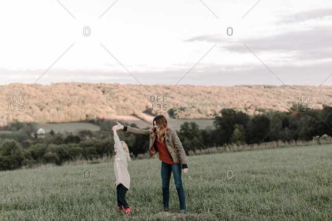 Mom and daughter dancing in a field
