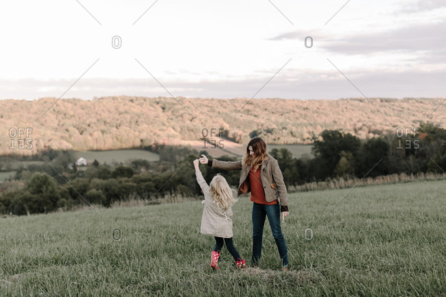 Mother and daughter dancing in a field