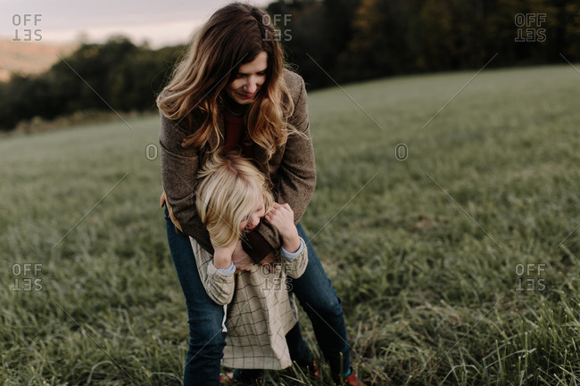 Mom wrapping arms around her daughter outdoors