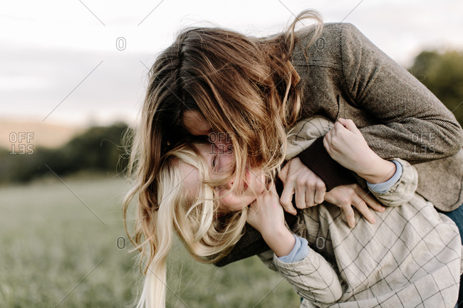 Mom embracing her daughter outdoors and kissing her cheek