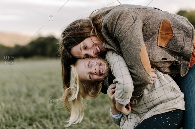 Mom embracing her young daughter outdoors