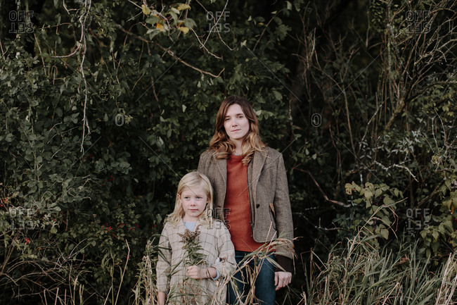 Portrait of mom and daughter standing at the edge of a forest